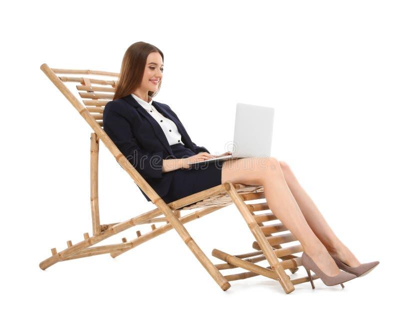 Молодая коммерсантка с ноутбуком на солнце против белой предпосылки Аксессуар пляжа стоковое изображение rf