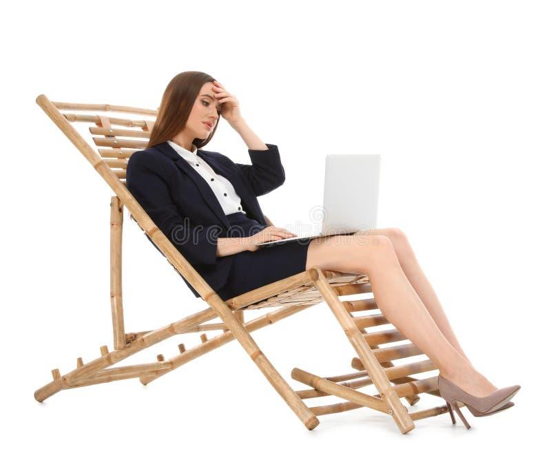 Молодая коммерсантка с ноутбуком на шезлонге против белой предпосылки E стоковое изображение