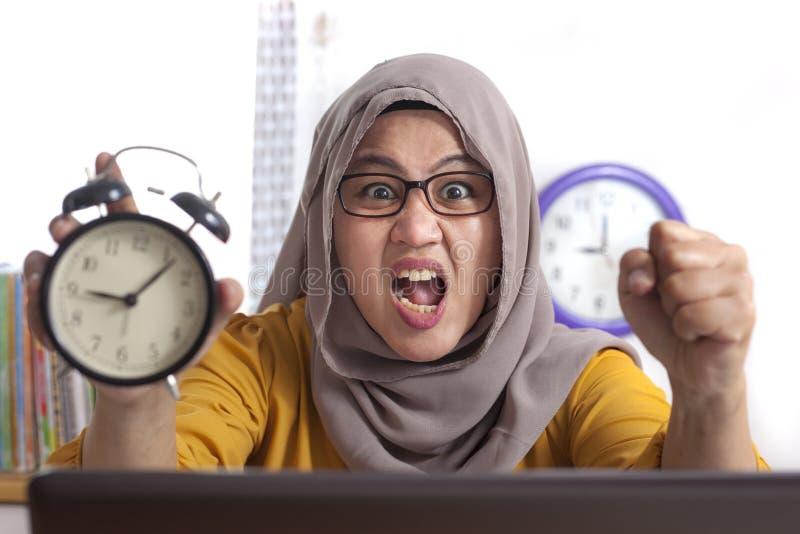 Молодая коммерсантка указывая на часы, сердитое выражение стоковое фото rf
