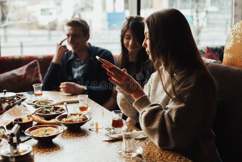 Молодая компания имеет потеху и ест в баре курить кальян, связывая в восточном ресторане стоковые фотографии rf