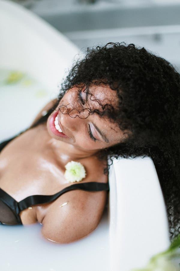 Молодая коричневая девушка кожи ослабляя в ванне с цветком на плече, нося черном купальнике Концепция спа и личной заботы стоковые фото