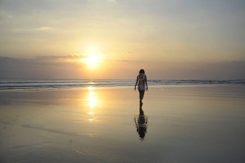 Молодая красивая азиатская женщина идя на берег моря песка свободно и ослабленный смотрящ горизонт солнца на пляже захода солнца стоковые фото
