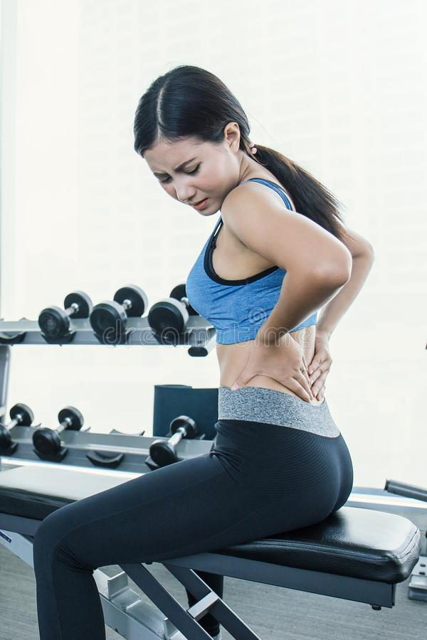 Молодая красивая азиатская женщина имея боль в ей назад стоковые фото