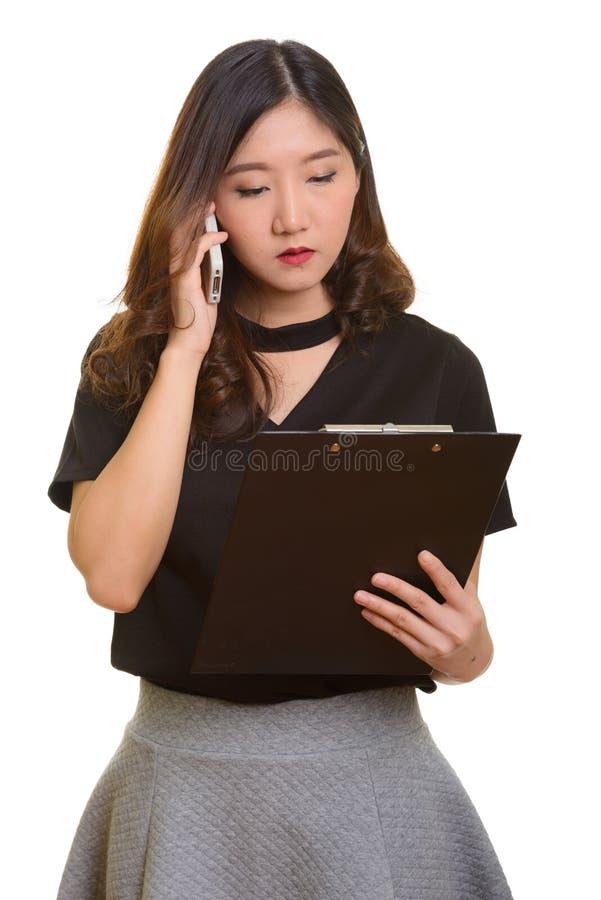 Молодая красивая азиатская коммерсантка говоря на whil мобильного телефона стоковые изображения