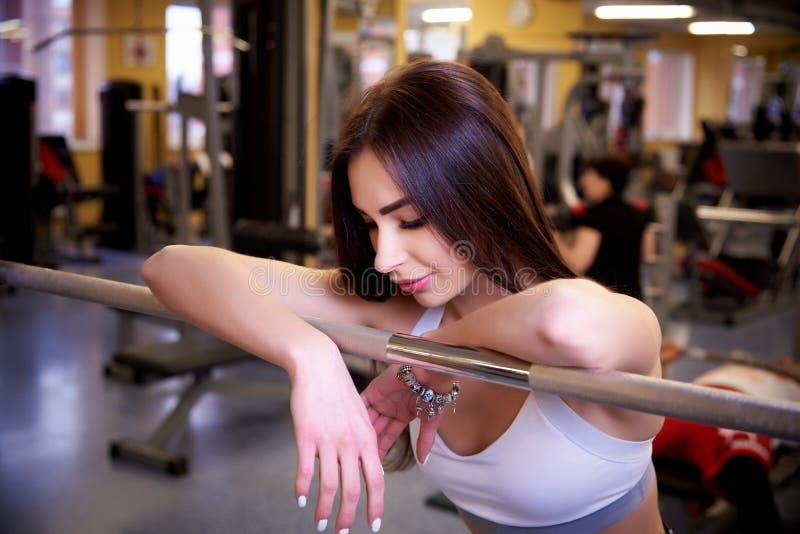 Молодая красивая атлетическая женщина около штанги в спортзале стоковое фото