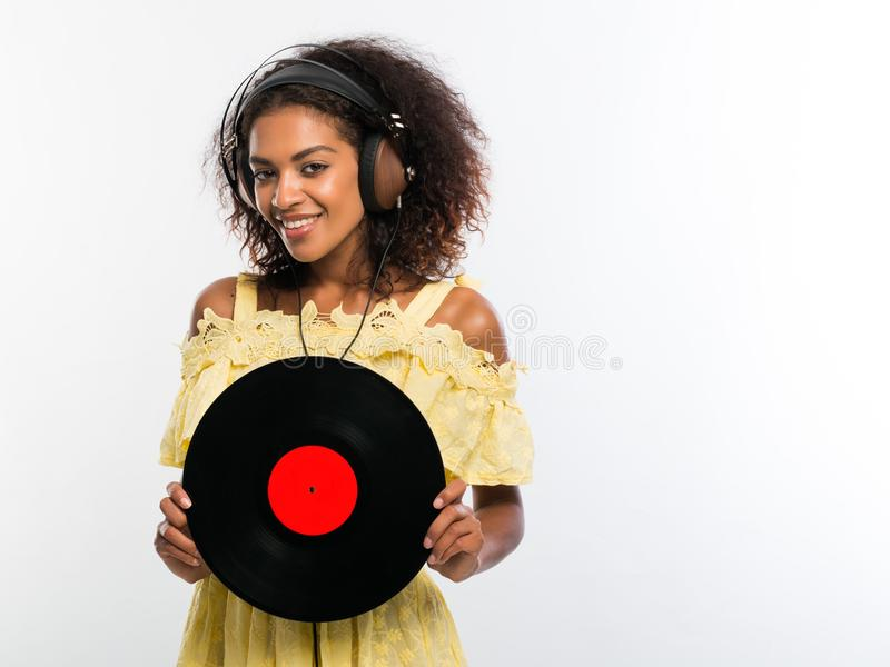 Молодая красивая Афро-американская женщина с наушниками в желтом платье наслаждаясь и танцуя с показателем винила на белизне стоковая фотография rf