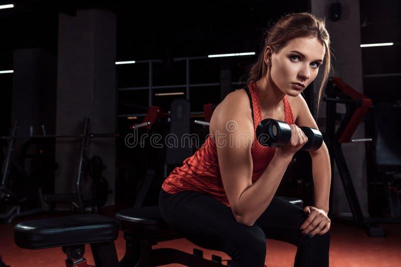 Молодая красивая белокурая девушка приниманнсяые за спорт тренируя с гантелями в спортзале Портрет стоковая фотография rf
