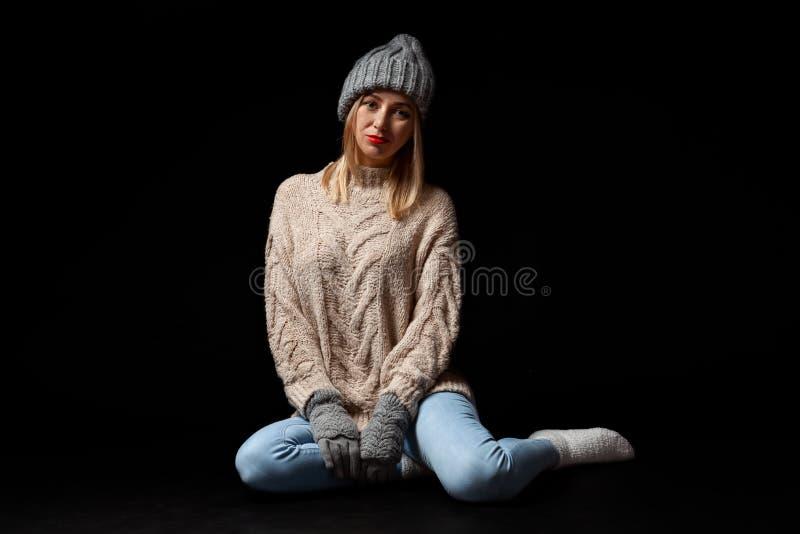 Молодая красивая белокурая женщина в связанных перчатках и шляпа в серых, голубых джинсах, бежевый свитер сидят на поле с пересеч стоковые изображения rf