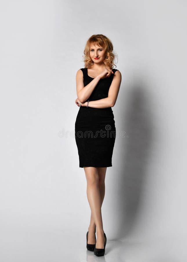 Молодая красивая белокурая женщина в теле черного маленького платья полном представляя на сером цвете стоковое изображение rf
