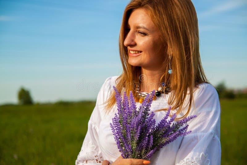 Молодая красивая белокурая женщина smilling с цветками в природе летом стоковые изображения rf