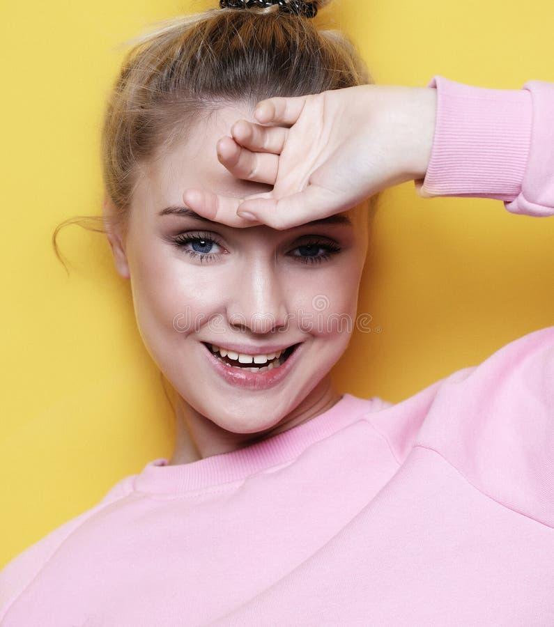 Молодая красивая белокурая жизнерадостная девушка усмехаясь смотрящ камеру над желтой предпосылкой стоковое фото