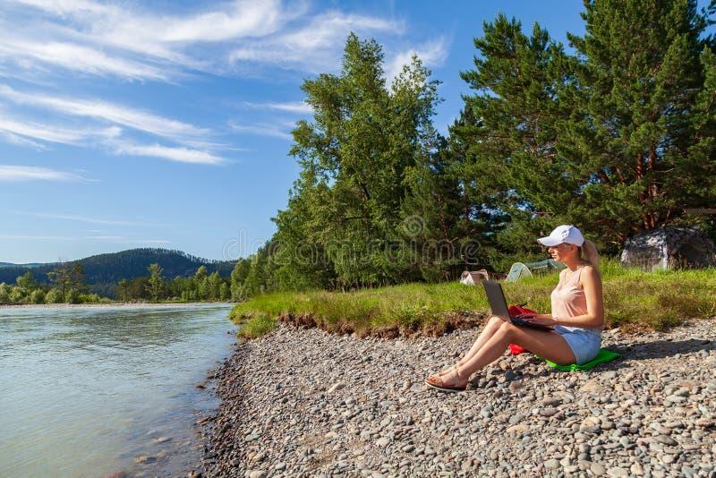 Молодая красивая блондинка женщины в шортах белой крышки и джинсовой ткани сидит на скалистом береге реки с ноутбуком на ее колен стоковые фотографии rf
