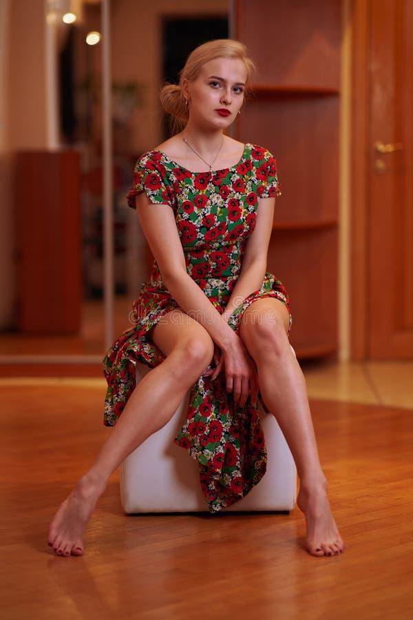 Молодая красивая блондинка с волосами собранными в chignon в платье флористической печати сидит на тахте в домашней установке, вы стоковое фото rf