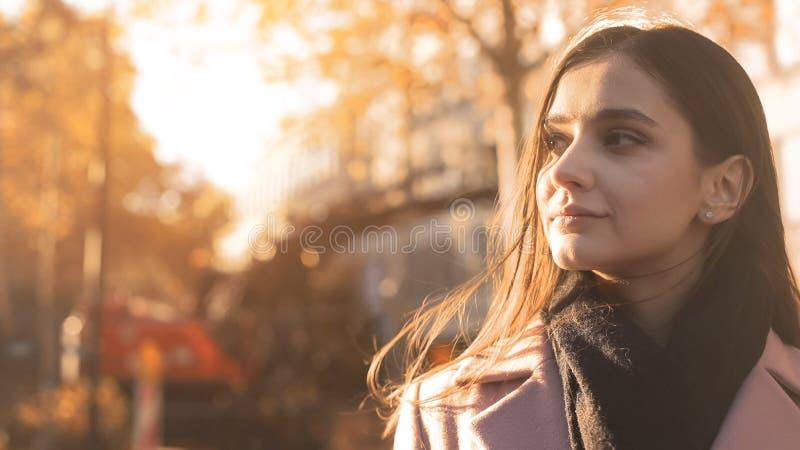 Молодая красивая дама наслаждаясь приятный мечтать большой, воодушевленность солнечного света осени стоковое фото