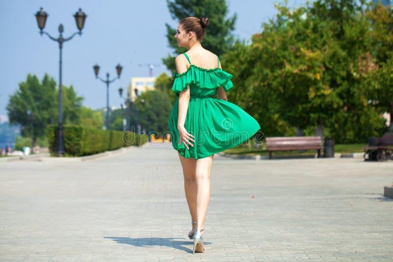 Молодая красивая девушка брюнета в зеленых прогулках платья вдоль обваловки реки Волга в самаре стоковые изображения