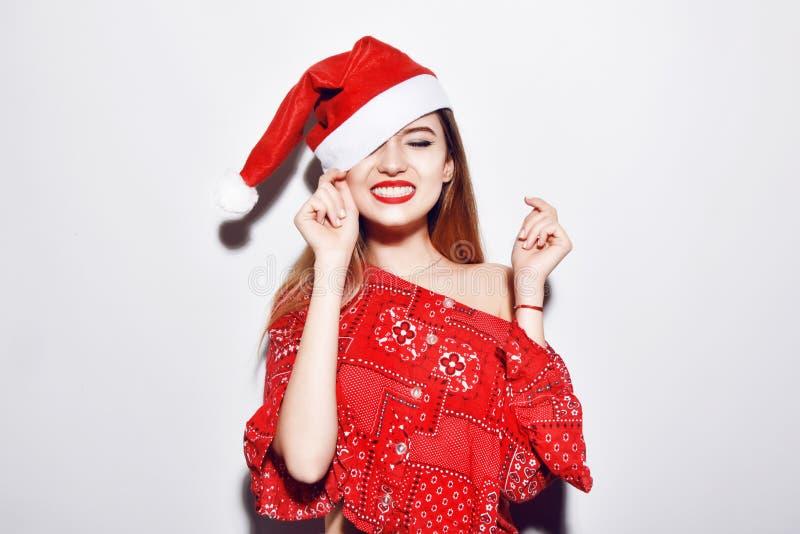 Молодая красивая девушка брюнет в усмехаться шляпы рождества Красные губы, красные шляпы стоковое фото