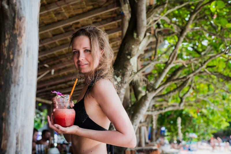 Молодая красивая девушка выпивая бутылку сока арбуза, держа стекло smoothie, вытрезвитель, здоровая еда, вкусная стоковые фото