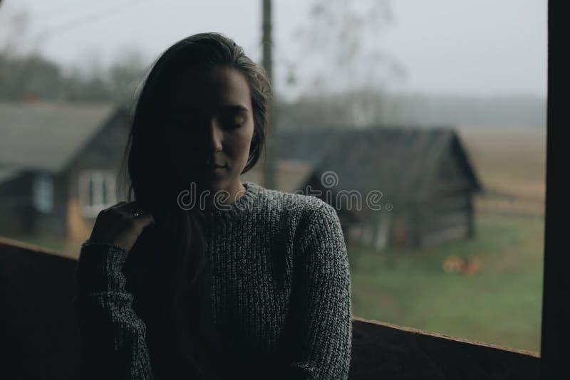 Молодая красивая девушка в деревне Модель на предпосылке деревянного дома в деревне темный свет стоковое фото