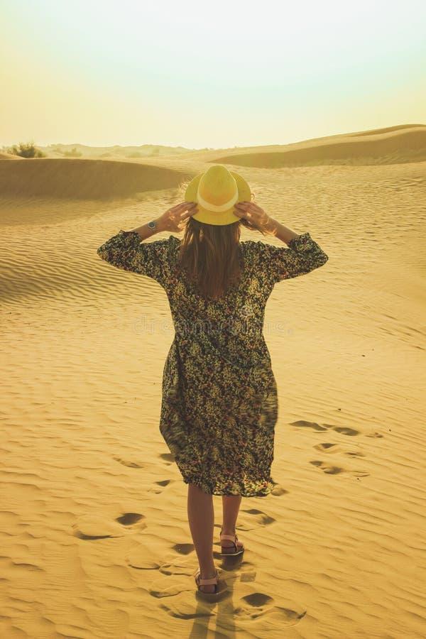 Молодая красивая девушка в длинном платье и шляпе в середине пустыни во время дневного времени стоковые изображения