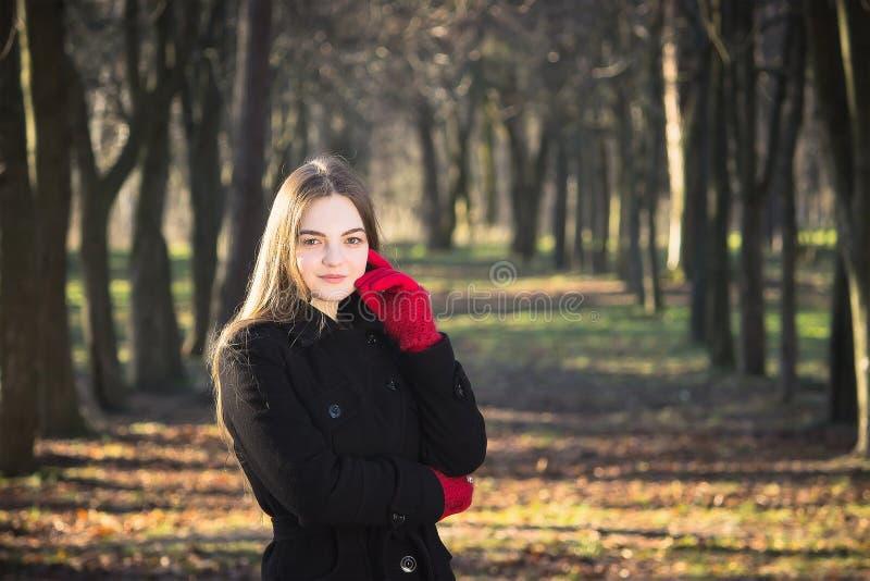 Молодая красивая девушка в перчатках черного пальто красных исследуя весну Forest Park стоковое изображение rf