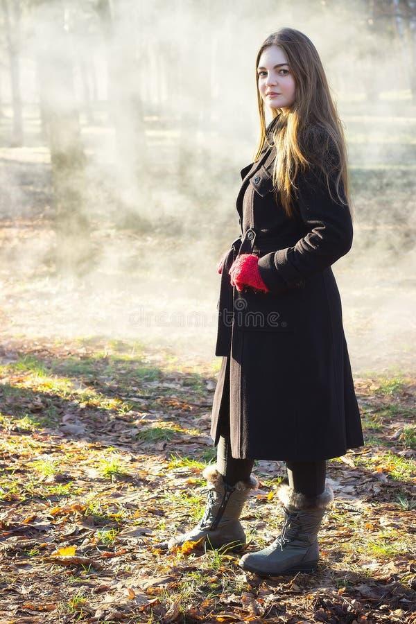 Молодая красивая девушка в перчатках черного пальто красных исследуя дым леса весны паркует стоковая фотография rf