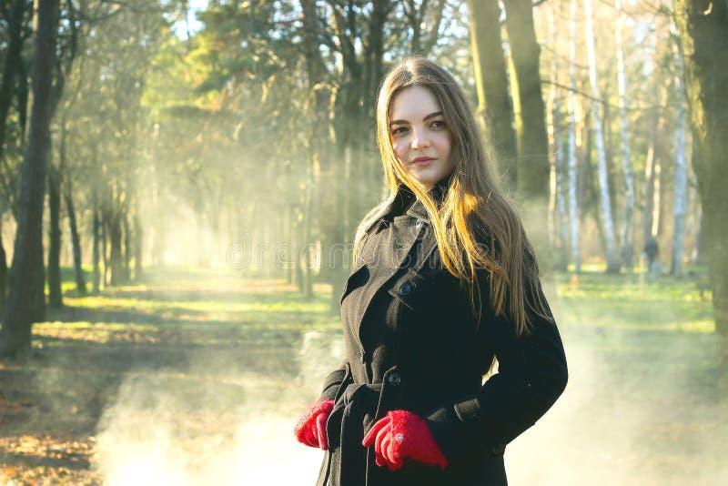 Молодая красивая девушка в перчатках черного пальто красных исследуя дым леса весны паркует стоковые фото
