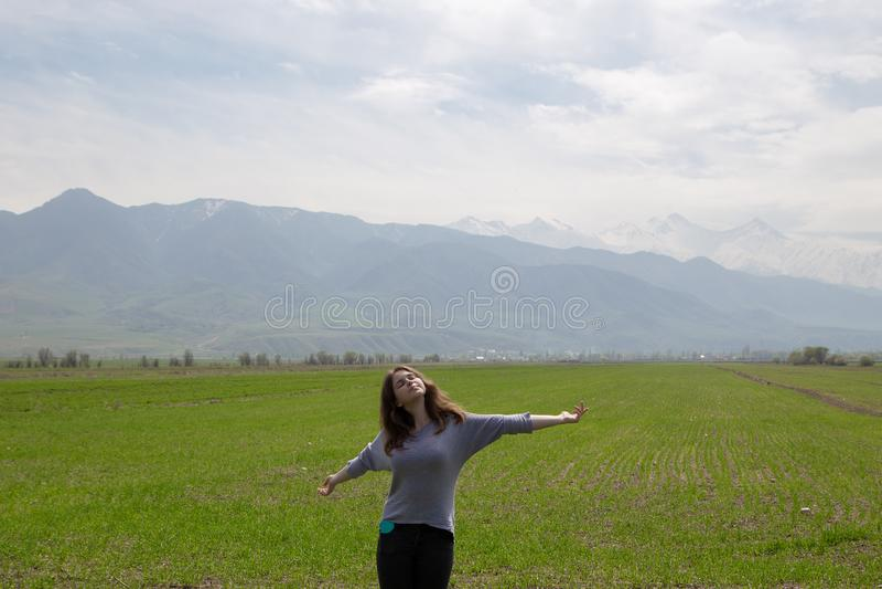 Молодая красивая девушка в природе Хорошее настроение на яркий весенний день Зеленые поля и голубые горы Туризм и перемещение стоковое изображение rf