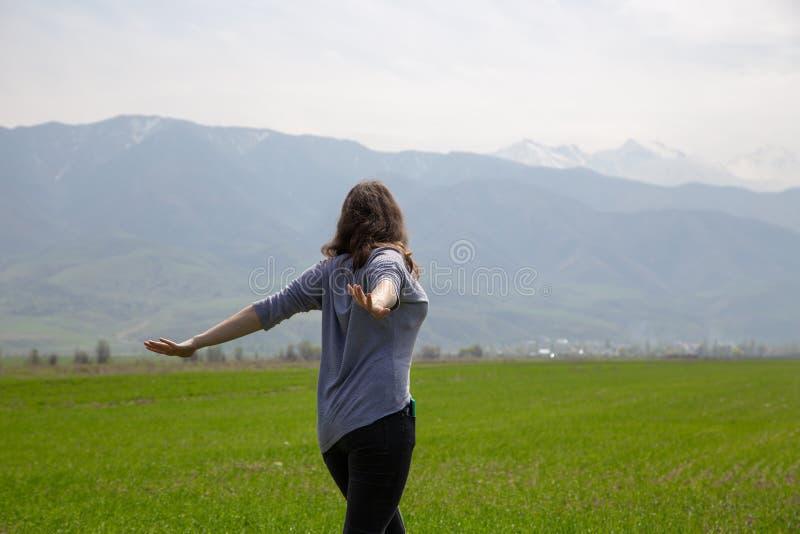 Молодая красивая девушка в природе Хорошее настроение на яркий весенний день Зеленые поля и голубые горы Туризм и перемещение стоковая фотография