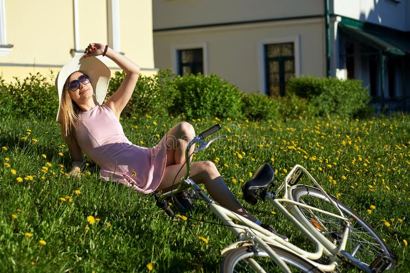 Молодая красивая девушка в солнечных очках, носящ шляпу, нося розовое платье, лежит на солнечном после полудня отдыхая на траве,  стоковые изображения rf