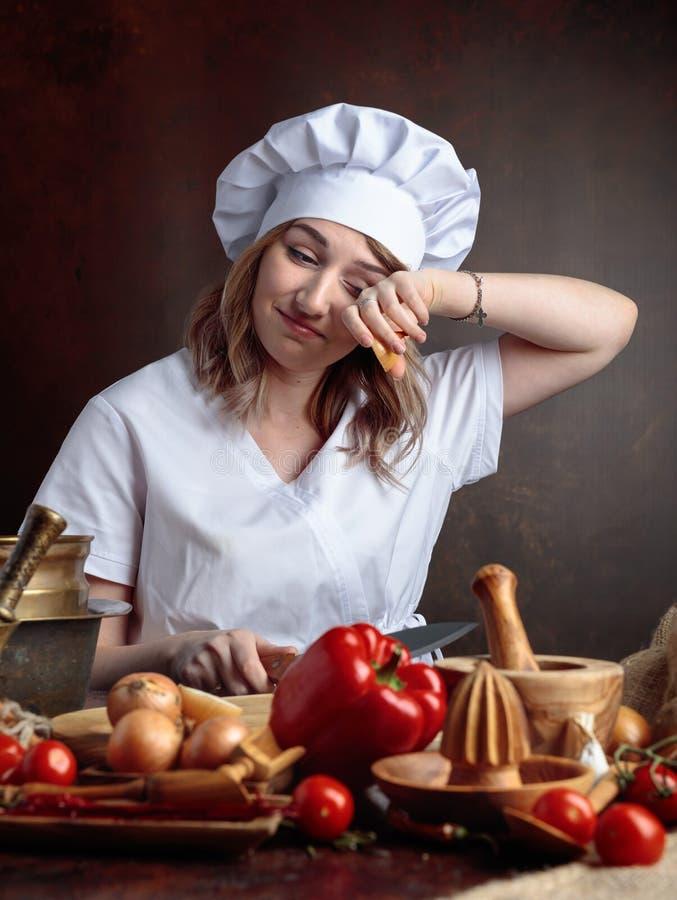 Молодая красивая девушка в форме шеф-повара режет луки стоковая фотография rf