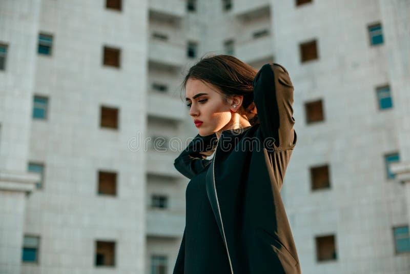 Молодая красивая девушка в черной куртке представляя против фона высокого Белого Дома стоковые фото
