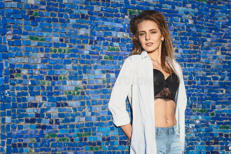 Молодая красивая девушка в unbuttoned белой рубашке на голубой предпосылке мозаики стоковое фото rf