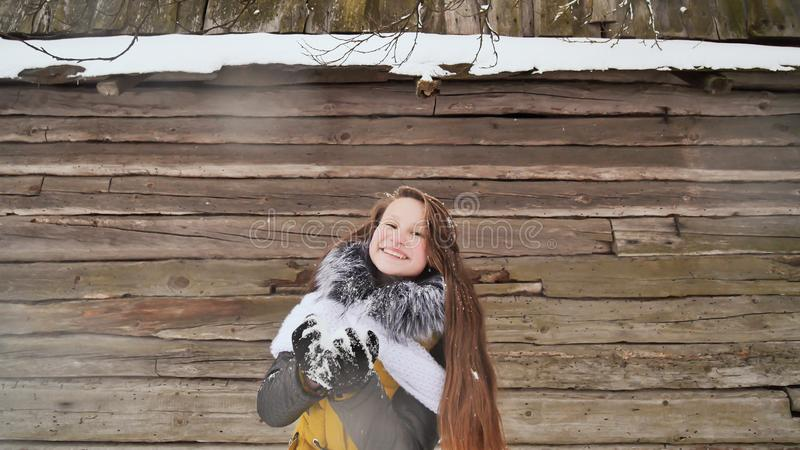 Молодая красивая девушка имея низовую метель потехи на камере в зиме одевает на предпосылке деревянного дома в стоковая фотография rf