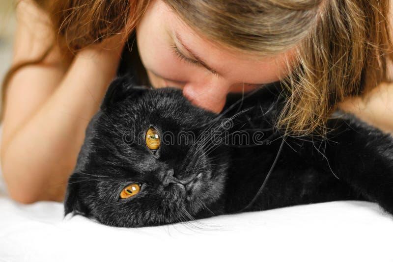 Молодая красивая девушка и черный Scottish складывают кота стоковые изображения rf