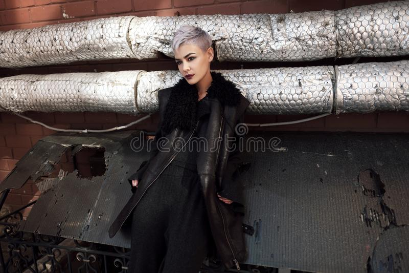 Молодая красивая девушка моды снимая outdoors около кирпичной стены на доме стоковое фото