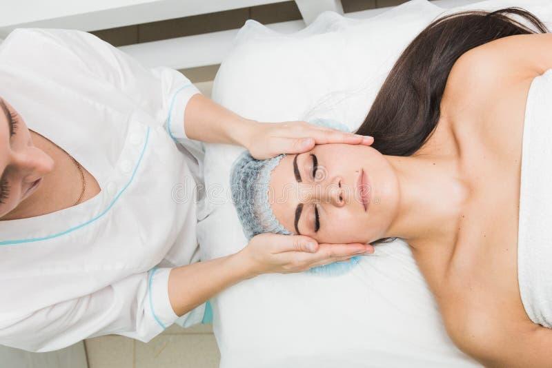 Молодая красивая девушка получая лицевой массаж в салоне красоты стоковые изображения rf