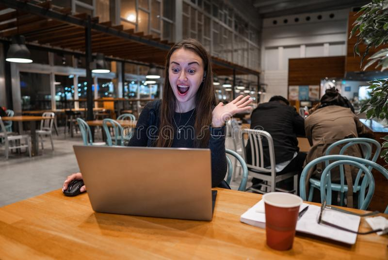 Молодая, красивая девушка работая с ноутбуком и выпивая кофе на деревянном столе стоковое фото rf