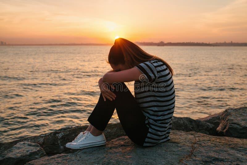 Молодая красивая девушка расстроена и плачущ покрывающ ее сторону с ее руками рядом с Bosphorus в Стамбуле в Турции стоковое изображение rf