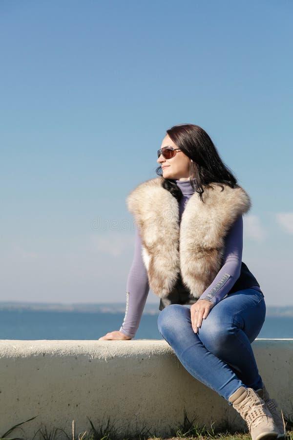 Молодая красивая девушка сидя на береге голубого моря стоковая фотография rf