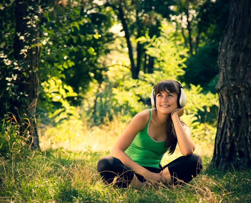 Молодая красивая девушка слушает к музыке в парке стоковое фото
