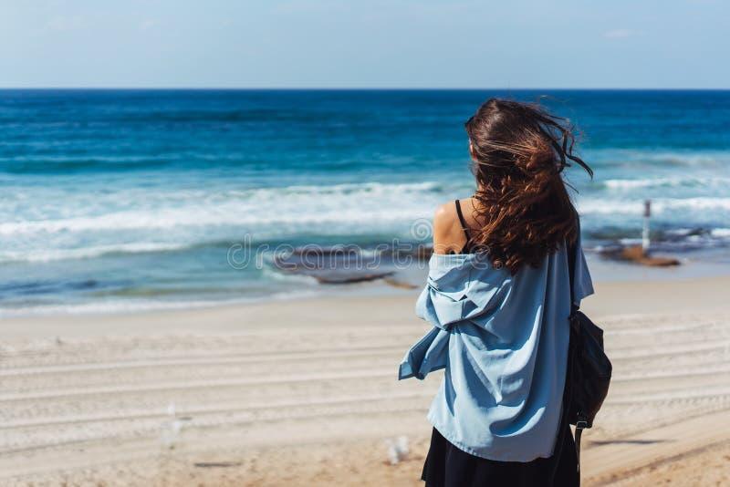 Молодая красивая девушка смотрит afar на море стоковые фото