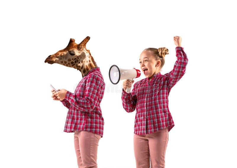 Молодая красивая девушка спорит с собой как жираф на белом фоне студии стоковое изображение