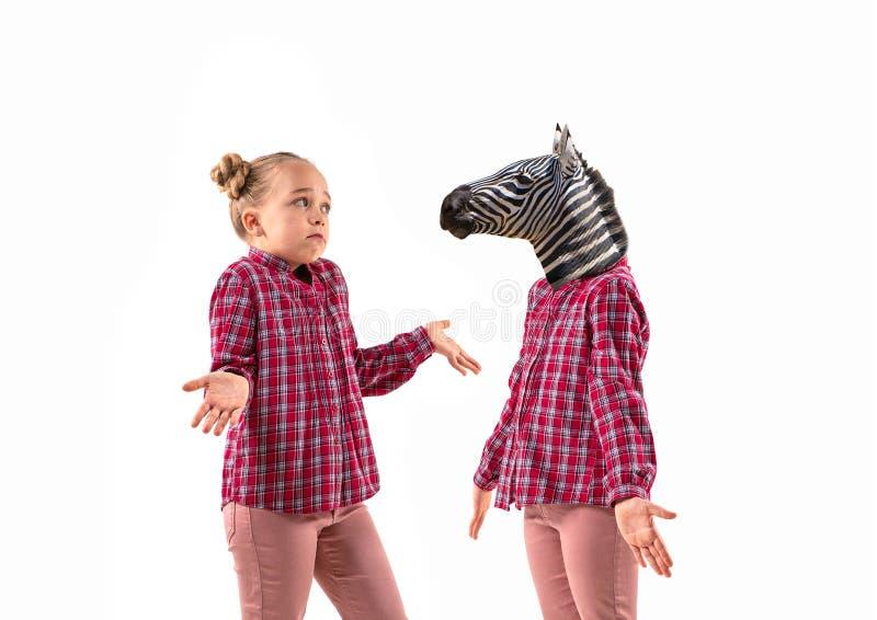 Молодая красивая девушка спорит с собой, как зебра на белом фоне студии стоковые фотографии rf