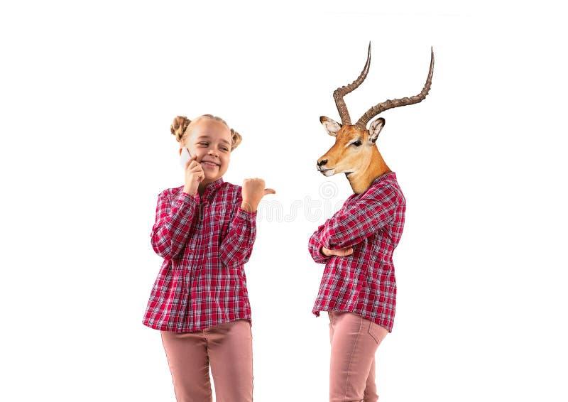 Молодая красивая девушка спорит с собой, как олень на белом фоне студии стоковая фотография