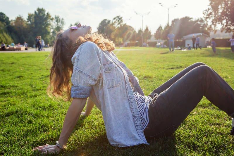 Молодая красивая девушка студентки отдыхая на траве в стоковые изображения rf