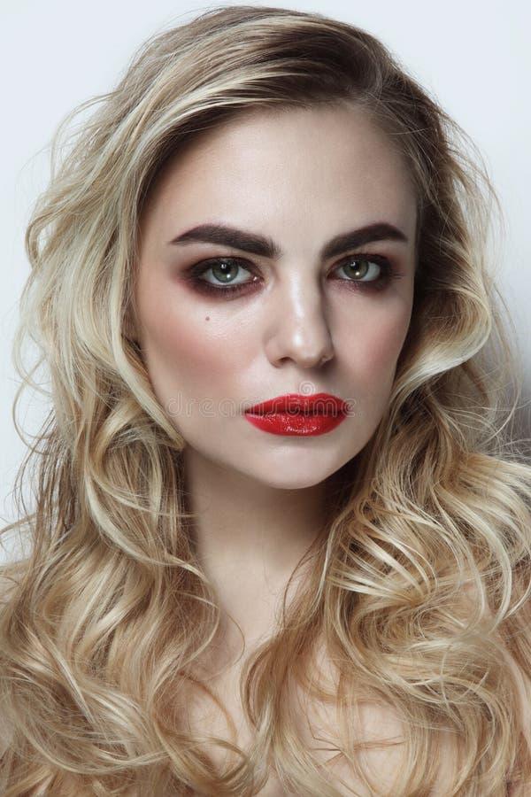 Молодая красивая девушка с белокурым вьющиеся волосы и красной губной помадой стоковая фотография rf