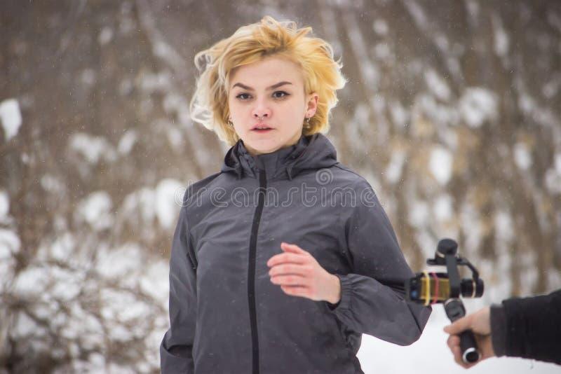 Молодая красивая женщина бежать в древесине зимы на камере стоковые фото