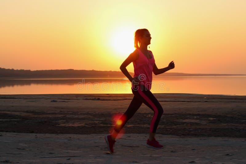 Молодая красивая женщина бежит вдоль seashore на оранжевой предпосылке захода солнца стоковые фото