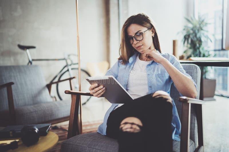 Молодая красивая женщина битника просматривая с прибором экрана касания на современном coworking месте работы стоковое изображение