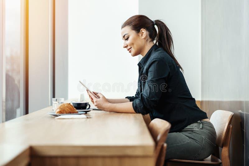 Молодая красивая женщина брюнет в кафе держа таблетку и усмехаться стоковые фото